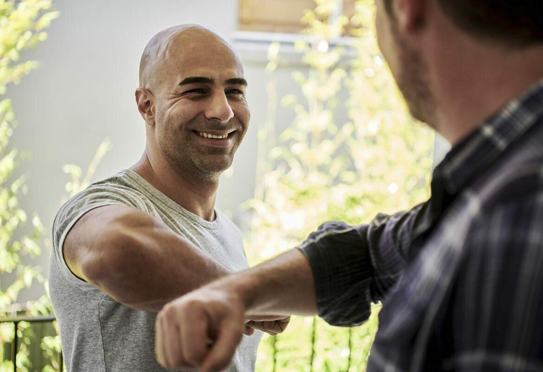 Man smiling at another man